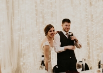 Bride and groom giving speech with a brightly lit white background