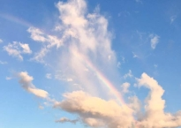 Narrow rainbow arched through dusty looking white clouds in a blue sky