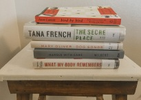 5 books stacked on a nightstand