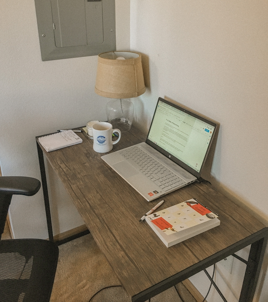 small brown, industrial desk tucked into a white walled corner with laptop, lamp, and coffee mug atop desk