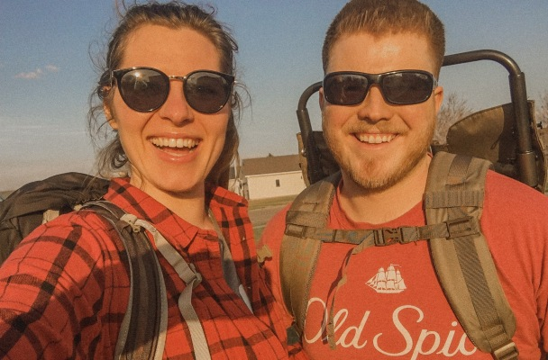 Picture of John and Alexis wearing red shirts standing outside with their backpack and hiking packs on.